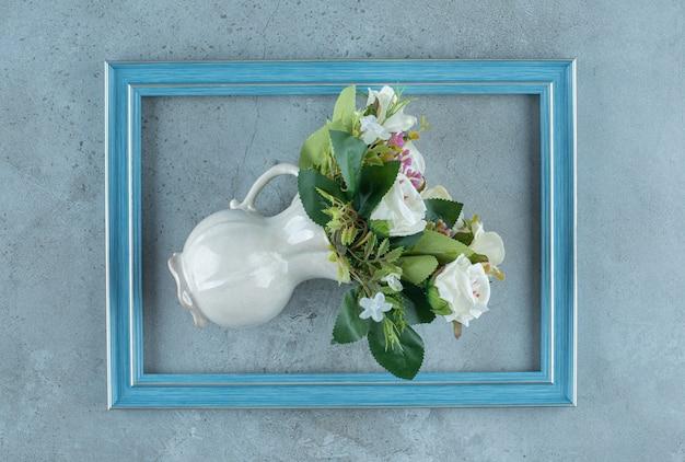 花瓶の白いバラの束は、大理石の背景のフレームの真ん中に倒れました。高品質の写真 無料写真