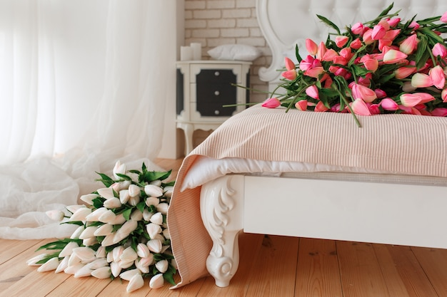 Bundle of tulips on bed in hotel apartment. Free Photo