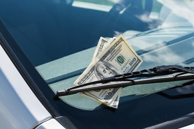 Bundle of us dollar banknotes left on a car under the car wiper on a windscreen Premium Photo