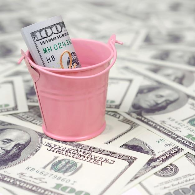A bundle of us dollars in a metal pink bucket on a set of dollar bills Premium Photo