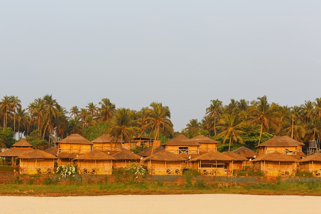 Bungalow on the coast of the sea, a network of houses from bamboo reed and palm leaves. cozy beach, goa, india. Premium Photo
