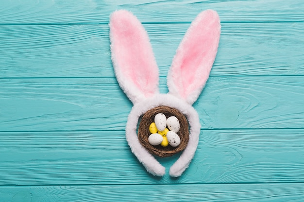Bunny ears and nest on wooden background Free Photo