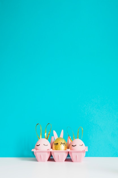 Bunny eggs in rack on blue Free Photo