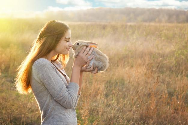 イースターのウサギとかわいいふわふわbunny.friendshipを保持しているrabbit.happy小さな女の子を持つ少女 Premium写真