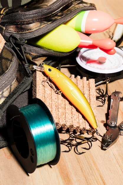 Buoy in bag; fishing lure and fishing reel on wooden desk Free Photo
