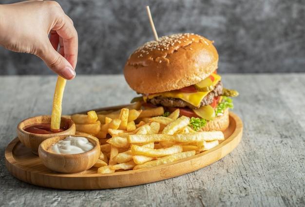 ハンバーガーとフライドポテトのソースと木製の大皿 無料写真