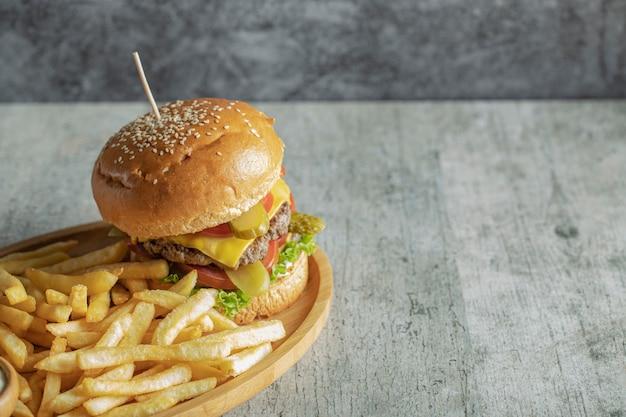 Бургер и жареный картофель в деревянной тарелке Бесплатные Фотографии