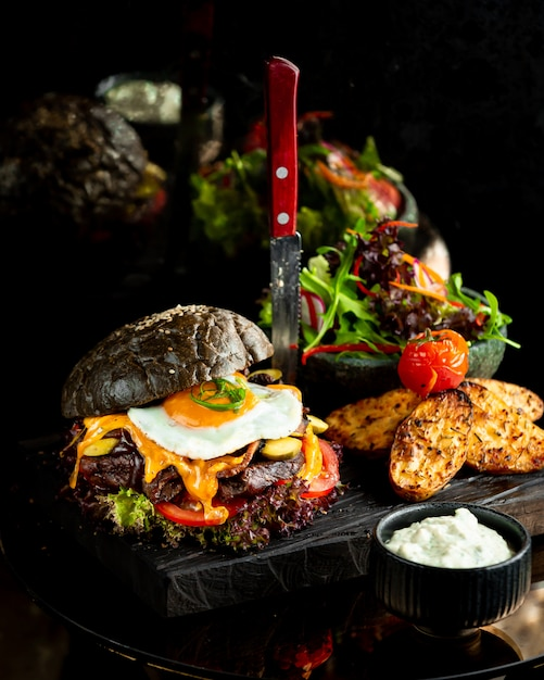 Burger in black bread bun with fried egg. Free Photo