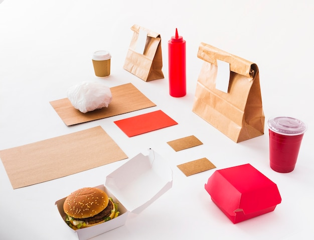 Burger; disposal cup; sauce bottle and food parcel on white backdrop Free Photo