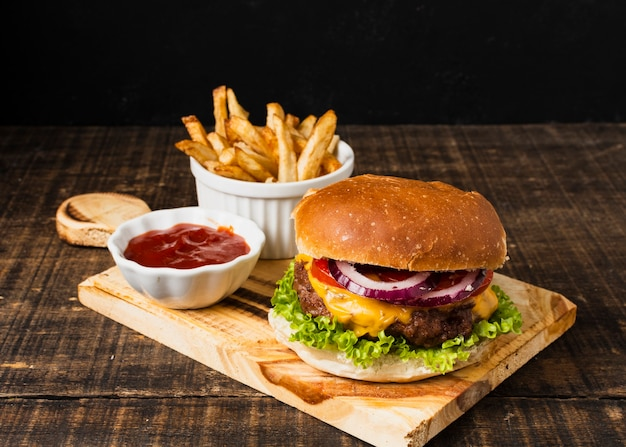 Burger and french fries on cutboard Free Photo