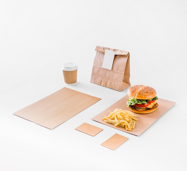Burger; french fries; parcel and disposal cup on white backdrop Free Photo