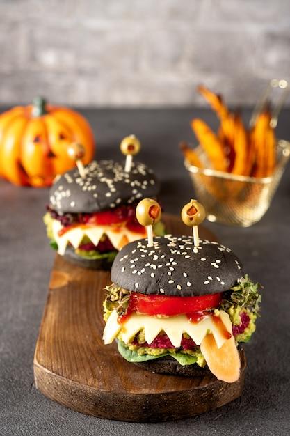 Burger monster for halloween celebration on dark Premium Photo