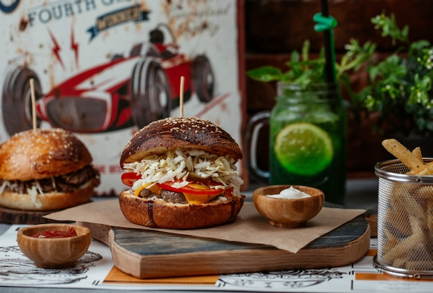 Burger with beef steak and salad inside served with a jar of mojito Free Photo