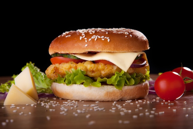 Burger with chicken and cheese, lettuce, cucumbers, tomatoes and onions on a black background. Premium Photo