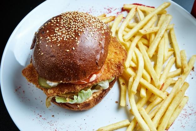 白い皿にフライドポテトのおかずにチキンカツ、トマト、キュウリ、レタスのハンバーガー。おいしいチキンバーガー。セレクティブフォーカス。ファストフード Premium写真