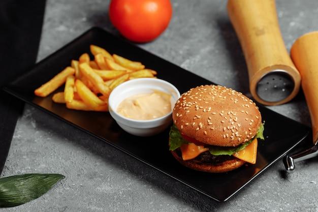 Бургер с котлетой, сыром и помидорами Premium Фотографии