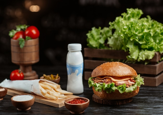 Burger with french fries on a wooden kitchen table Free Photo
