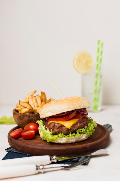 Burger with fries on wood plate Free Photo