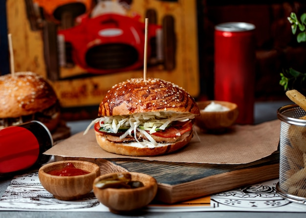 Burger with ham tomatoes and cabbage Free Photo