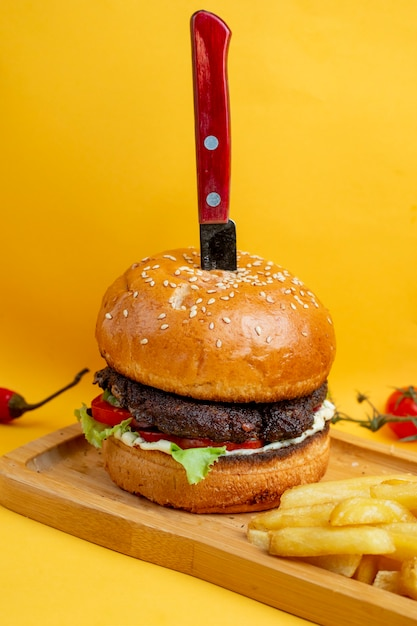 Burger with knife inside and fries Free Photo