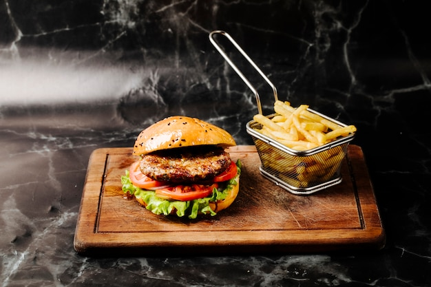 Burger with meat , tomato and lettuce served with french fries. Free Photo