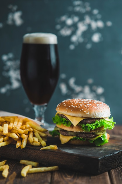 Burger with potatoes and dark beer on a wooden board on a blue-gray background Premium Photo