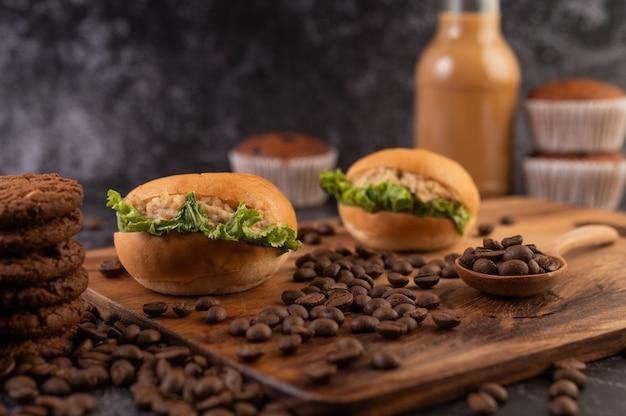カップケーキやコーヒー豆など、木製のまな板付きバーガー。 無料写真