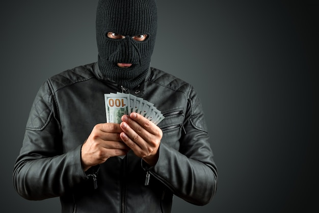 Burglar in a balaclava holds dollars in his hands on a dark background Premium Photo