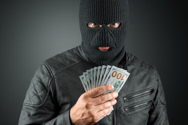 Burglar in a balaclava holds dollars in his hands on a dark background Premium Photo