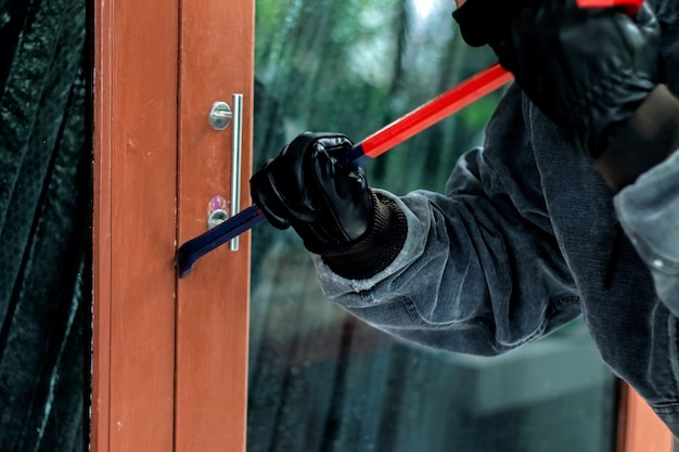 Burglar with crowbar trying break the door to enter the house Premium Photo