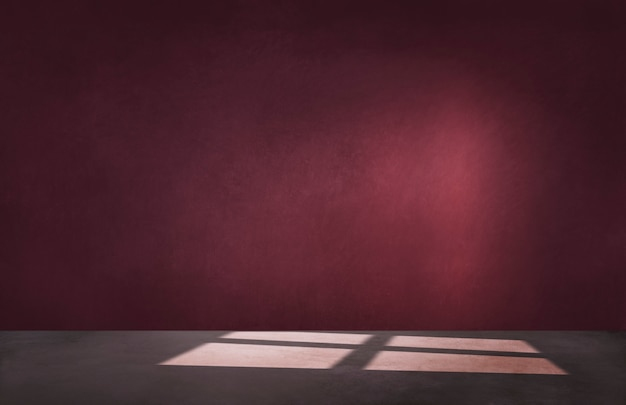 Burgundy red wall in an empty room with concrete floor Premium Photo