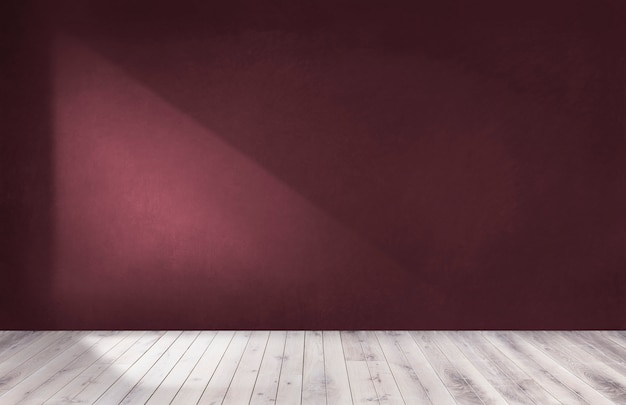 Burgundy red wall in an empty room with a wooden floor Premium Photo