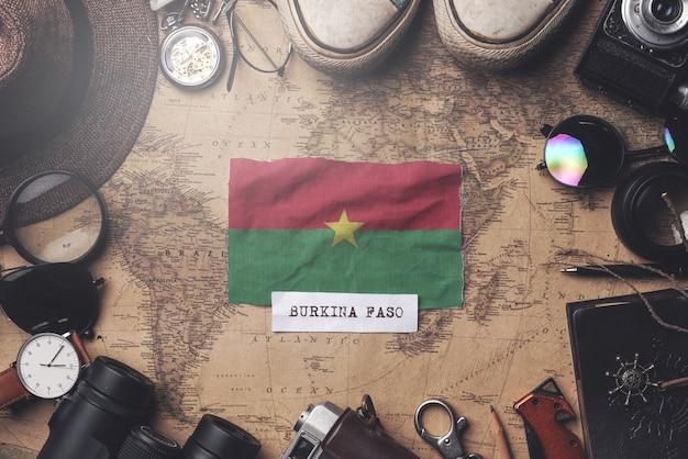 古いビンテージ地図上の旅行者のアクセサリー間のブルキナファソの旗。オーバーヘッドショット Premium写真