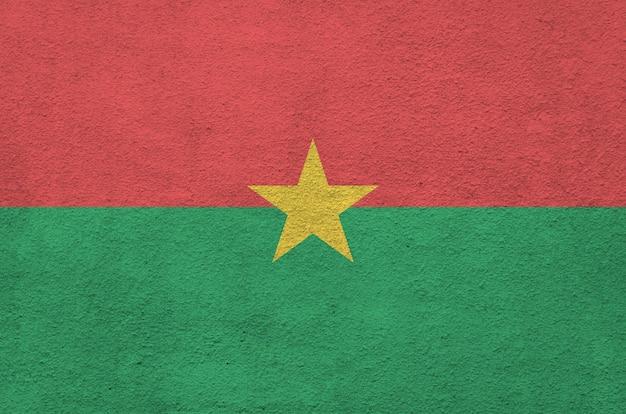 古いレリーフの左官壁に明るいペンキ色で描かれたブルキナファソの旗。 Premium写真