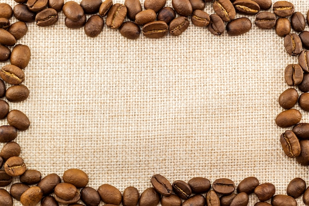 Burlap sackcloth canvas and coffee beans placed round in circle photo background. copy space. coffee border Premium Photo