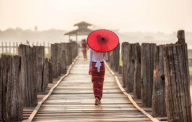 Burmese woman holding traditional red umbrella and walking on u bein bridge Premium Photo