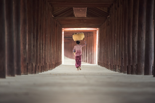 Burmese woman putting bamboo basket on head Premium Photo