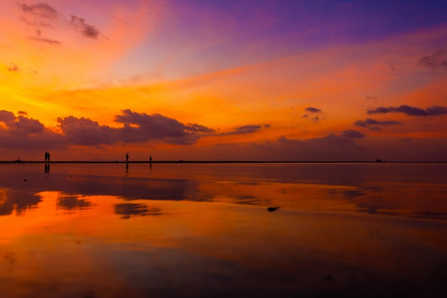 Горящее яркое небо во время заката на тропическом пляже. закат во время исхода, сила людей, гуляющих по воде Premium Фотографии
