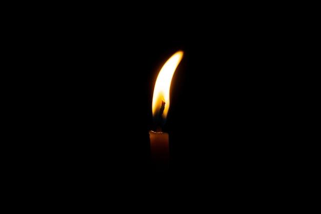 Burning candle on black background Premium Photo