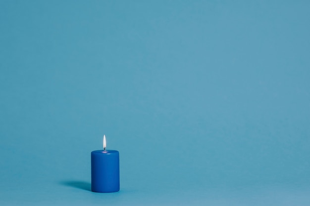 Burning candle in blue color Free Photo