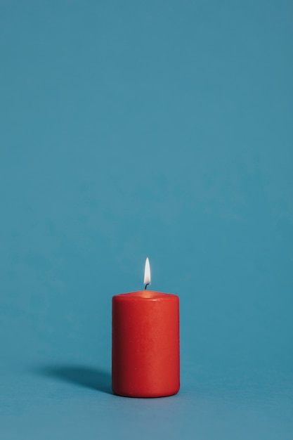 Burning candle in red color Free Photo