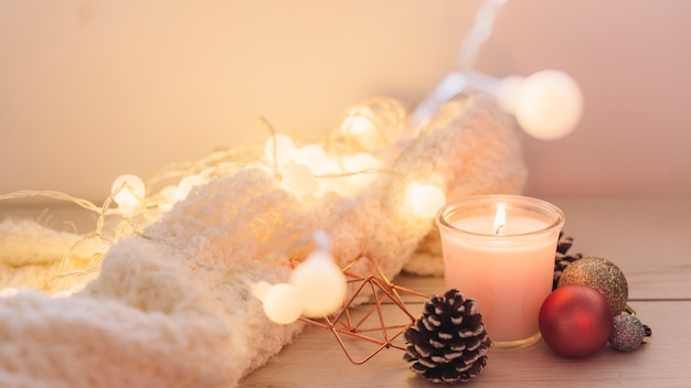 Burning candle with scarf on table Premium Photo