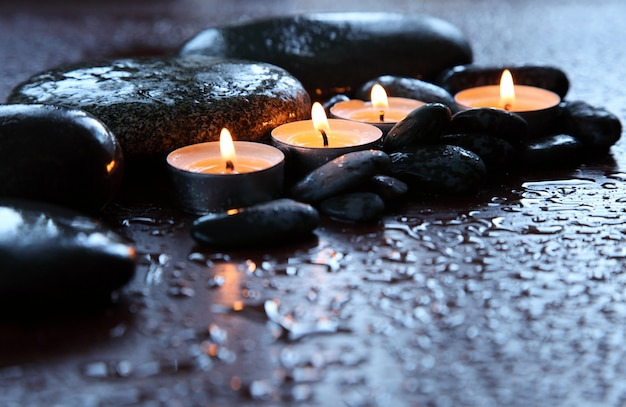 Burning candles and drops of water. stone therapy. spa treatments. Premium Photo