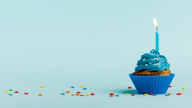 Burning candles on muffins with star sprinkles against blue backdrop Free Photo