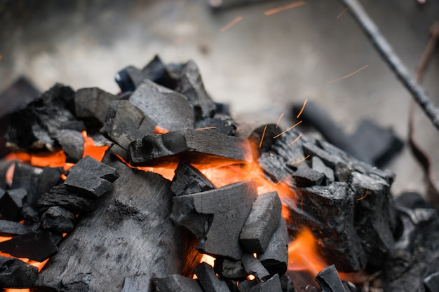 Burning charcoal close-up. coal in fire and smoke. Premium Photo
