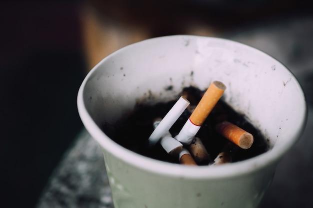 背景に灰皿のタバコを燃やす。喫煙エリアには、紙カップにタバコのスタブがあります。 Premium写真