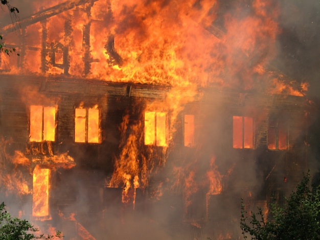Burning house, big wooden building completely destroyed by fire Premium Photo