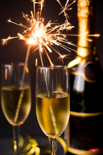 Burning sparkler in champagne glass on dark background Free Photo