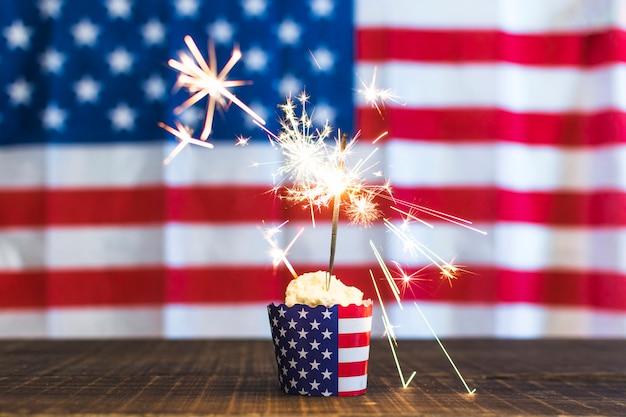 Burning sparkler on cupcake against defocused usa flag background Free Photo