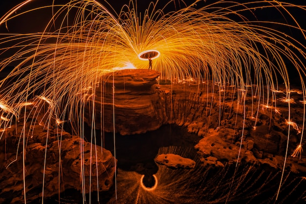 Burning steel wool on the rock near the river. Premium Photo